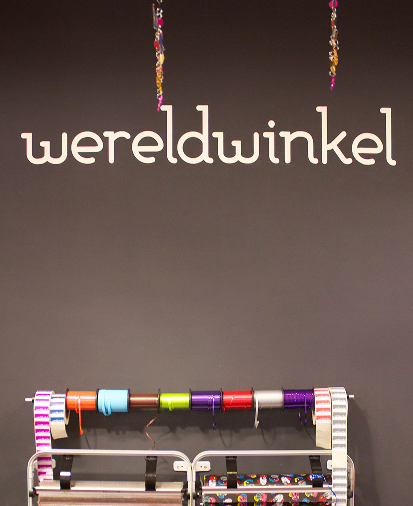 Wereldwinkel-logo achter kassabalie met decoratief inpakmateriaal